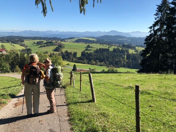 Wanderer blicken über eine sommerliche Berglandschaft